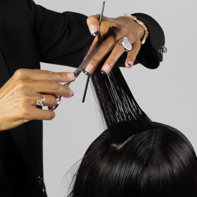 Lift hair 90 degrees and cut from shorter in the back to longer in the front, creating a concave layer that helps remove weight while maintaining length